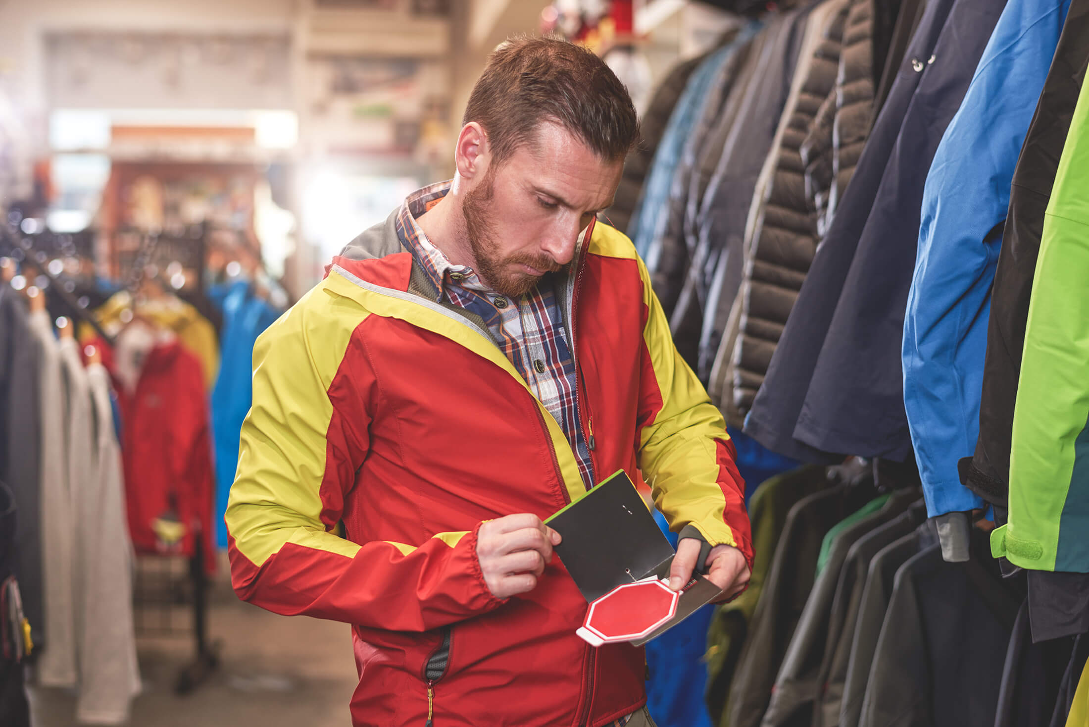 Men trying on a jacket and looking at tag
